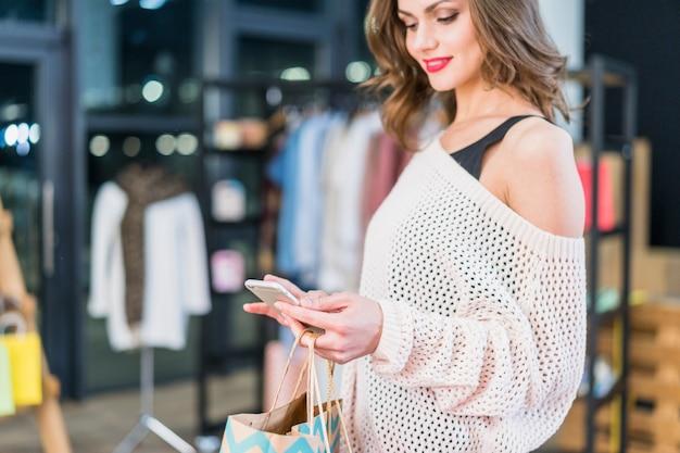 Moda mulher olhando para celular segurando sacolas de compras na mão Foto gratuita