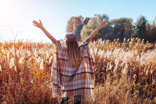 Moda outono. jovem mulher que veste o poncho à moda ao ar livre. roupas e acessórios. garota feliz, levantando as mãos Foto Premium