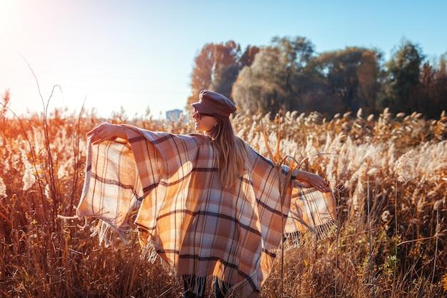 Moda outono. jovem mulher vestindo roupa elegante ao ar livre Foto Premium
