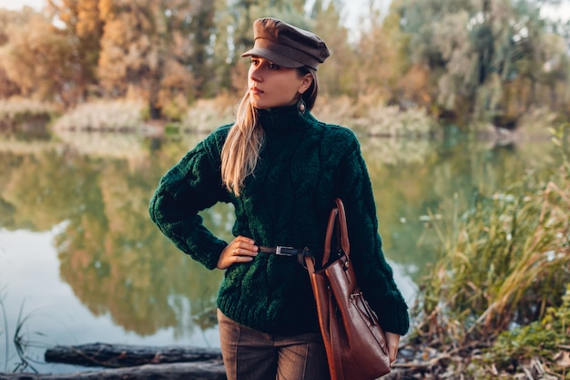 Moda outono. jovem mulher vestindo roupa elegante e segurando a bolsa ao ar livre. roupas e acessórios Foto Premium