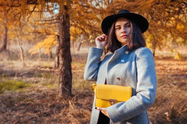 Moda outono. jovem mulher vestindo roupa elegante e segurando a bolsa ao ar livre Foto Premium