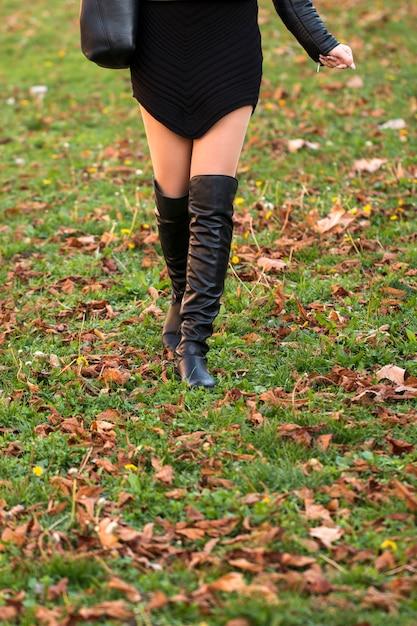 Moda outono, sapatos nas pernas da mulher em folhas no chão Foto Premium