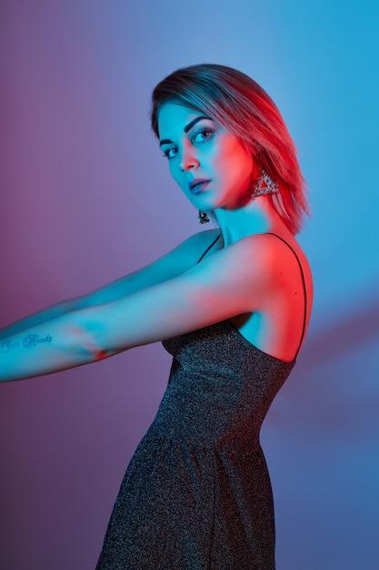Moda retrato menina luz lâmpadas de néon azul cor vermelha. mulher posando em maquiagem colorida, linda. Foto Premium