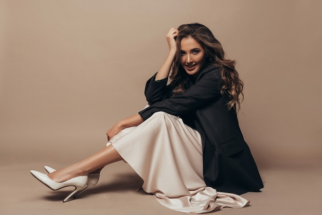 Modelo alegre sentada no chão, vestindo uma jaqueta preta grande e moderna e um vestido longo cremoso, sapatos de salto alto nos pés. penteado cacheado e maquiagem Foto gratuita
