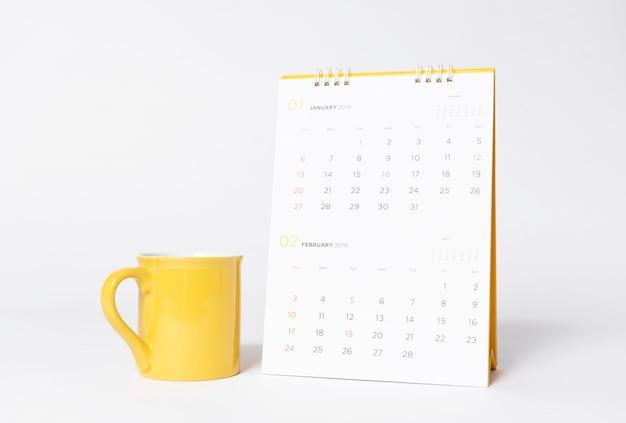 Modelo amarelo vazio do tampão e ano civil espiral de papel 2019 no fundo cinzento. Foto Premium