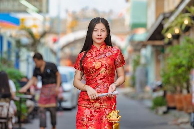 Modelo asiático bonito que veste o ano novo chinês tradicional de cheongsam.happy Foto Premium