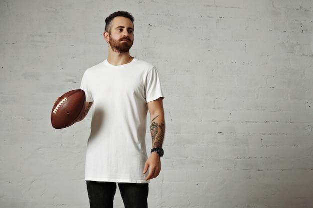 Modelo barbado e tatuado em uma camiseta de manga curta branca simples segurando uma bola de futebol de couro na parede cinza Foto gratuita