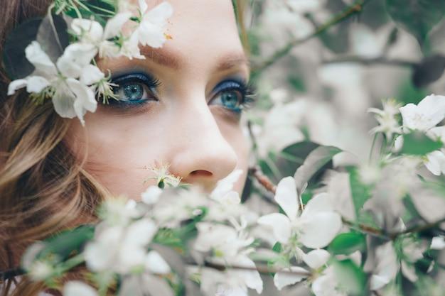 Modelo bonito da menina com composição brilhante entre as flores brancas. retrato, de, um, mulher, close-up Foto Premium
