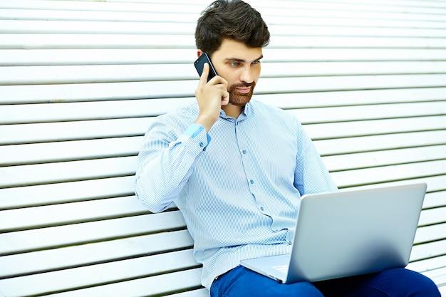 Modelo bonito jovem empresário sério sentado no banco do parque usando o laptop em pano casual hipster falando no celular Foto gratuita