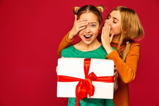 Modelo cobrindo os olhos de sua amiga e dando-lhe grande caixa de presente e haring segredo Foto gratuita