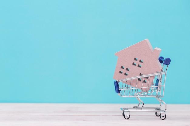 Modelo da casa de madeira no carrinho de compras na mesa de madeira Foto Premium