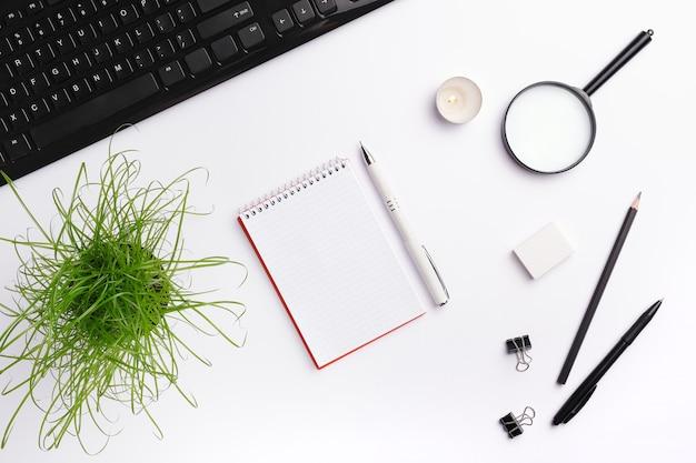 Modelo de área de trabalho de mesa de escritório em casa com teclado preto, notebook, vela, caneta, planta e outros acessórios de escritório. Foto Premium