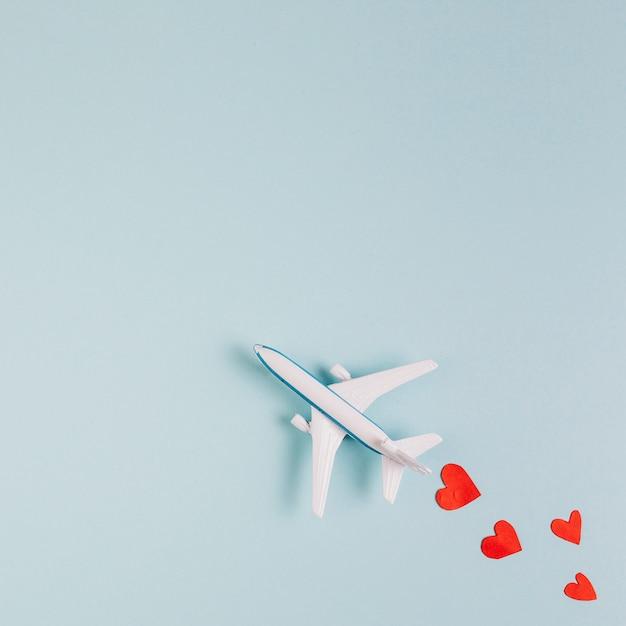 Modelo de avião de brinquedo com corações lidos Foto gratuita