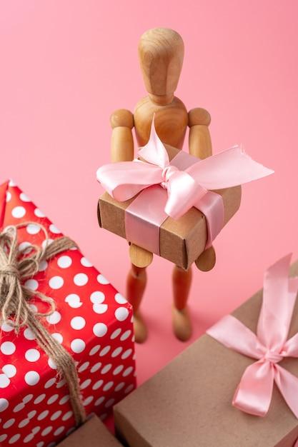 Modelo de brinquedo de madeira segurando presentes. cartão de férias para dia dos namorados e dia das mulheres Foto Premium