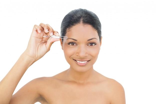 Modelo de cabelo preto alegre removendo os cabelos de sua sobrancelha Foto Premium