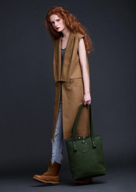 Modelo de cabelo vermelho, segurando o grande saco de couro verde sobre fundo escuro. garota vestindo jaqueta sem mangas, com jeans e botas. Foto Premium