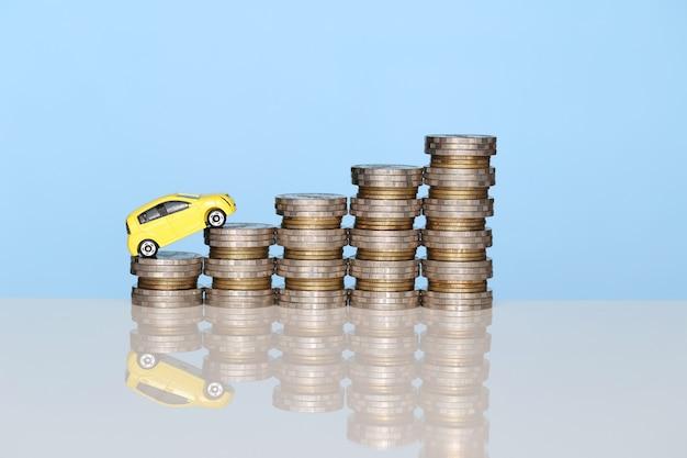 Modelo de carro amarelo em miniatura na crescente pilha de moedas dinheiro em fundo azul Foto Premium