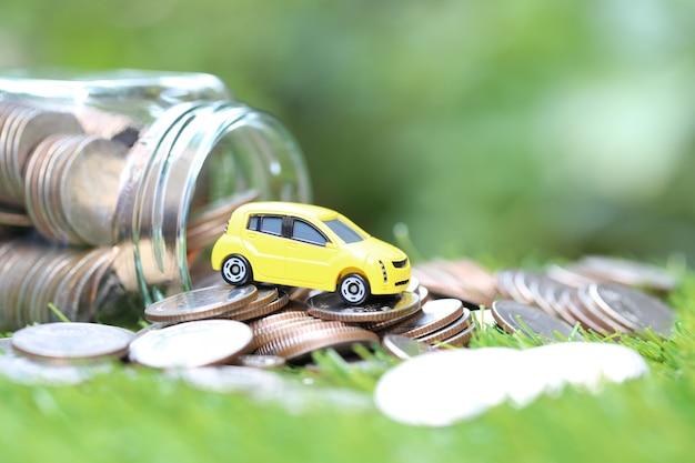 Modelo de carro amarelo em miniatura na pilha de moedas dinheiro em frasco de vidro no fundo de natureza verde Foto Premium