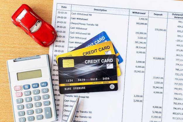 Modelo de carro e calculadora no extrato bancário e cartão de crédito em uma mesa de madeira. Foto Premium