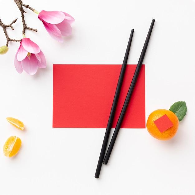Modelo de cartão e pauzinhos ano novo chinês Foto gratuita