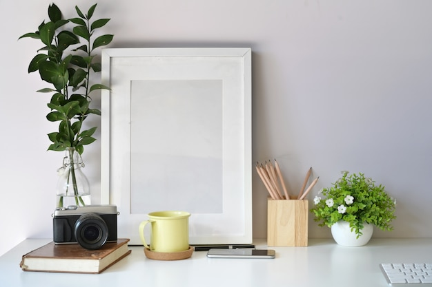 Modelo de cartaz de maquete com câmera vintage, suprimentos no espaço de trabalho de mesa branca Foto Premium
