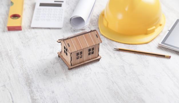 Modelo de casa com ferramentas em fundo branco Foto Premium