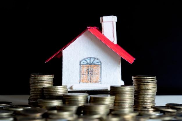 Modelo de casa com moedas na mesa de madeira Foto gratuita