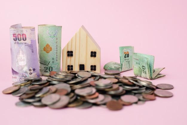 Modelo de casa de madeira com notas da moeda tailandesa e moedas de dinheiro para o conceito de negócio, finanças e investimentos imobiliários Foto Premium
