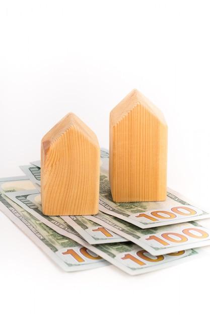 Modelo de casa de madeira com notas de dólares, conceito imobiliário Foto Premium