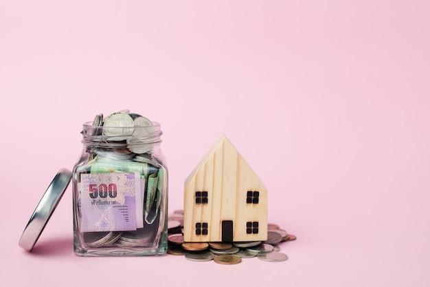 Modelo de casa de madeira com notas e dinheiro moeda tailandesa moedas no frasco de vidro para negócios, finanças e conceito de investimento imobiliário Foto Premium