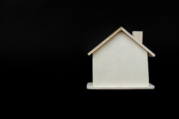 Modelo de casa de madeira contra o fundo preto Foto gratuita