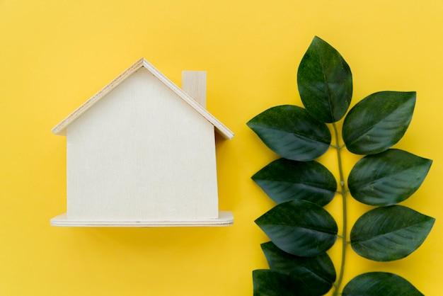 Modelo de casa de madeira perto das folhas verdes contra fundo amarelo Foto gratuita