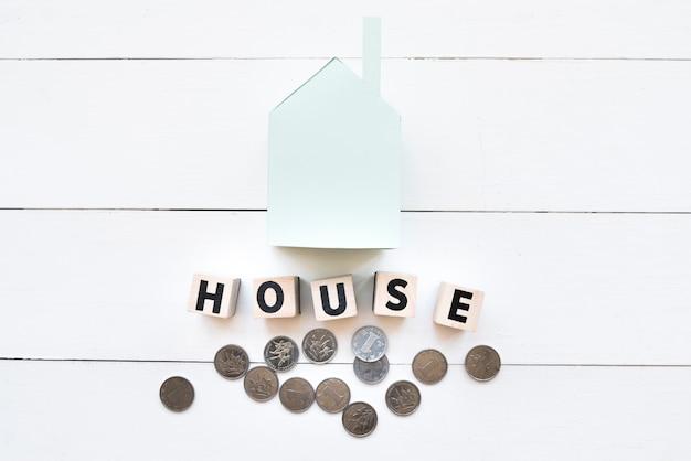 Modelo de casa de papel azul com blocos de madeira e moedas no pano de fundo branco de madeira Foto gratuita