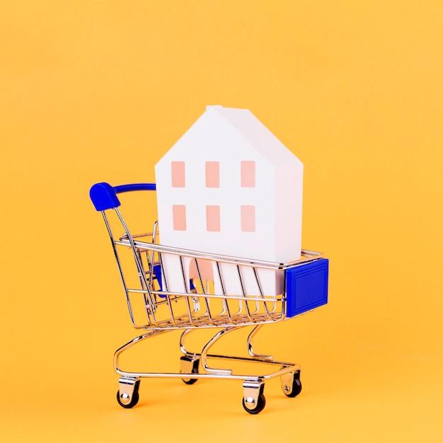 Modelo de casa dentro do carrinho de compras contra pano de fundo amarelo Foto gratuita