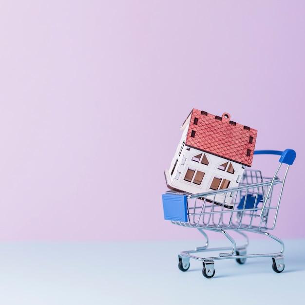 Modelo de casa no carrinho de compras em miniatura Foto gratuita