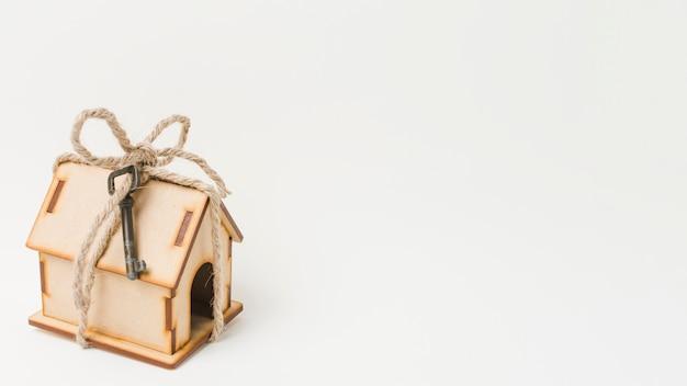 Modelo de casa pequena amarrado com corda e chave vintage isolado com fundo branco Foto gratuita