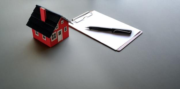 Modelo de casa pequena com papel de nota e caneta Foto Premium