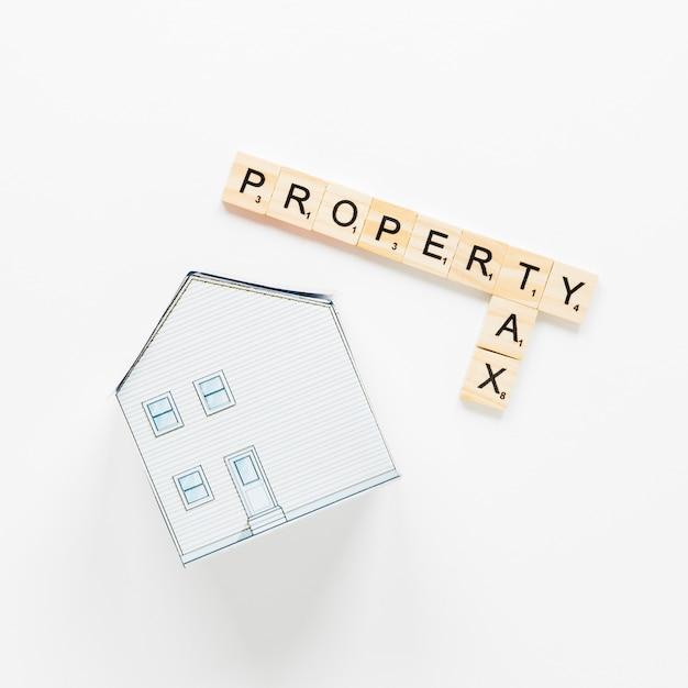 Modelo de casa perto de blocos com texto de propriedade e impostos sobre fundo branco Foto gratuita