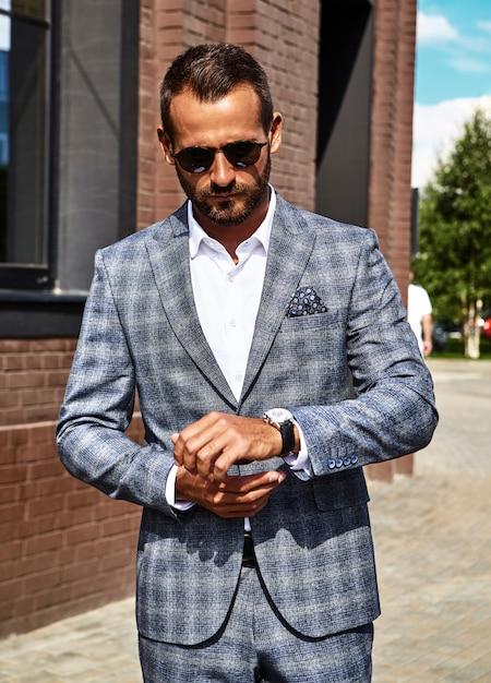 Modelo de empresário de moda bonito vestido elegante terno xadrez posando na rua Foto gratuita