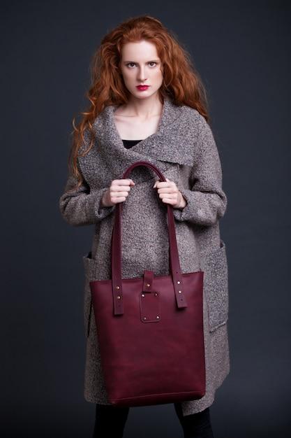 Modelo de forma de cabelo vermelho segurando o saco de couro vermelho escuro grande sobre fundo escuro. garota vestindo jumper longo. Foto Premium