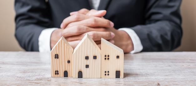 Modelo de madeira para casa na mesa do escritório com o jovem empresário. Foto Premium