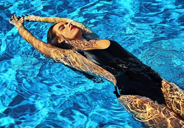 Modelo de menina bonita com cabelos escuros na moda praia preta Foto gratuita
