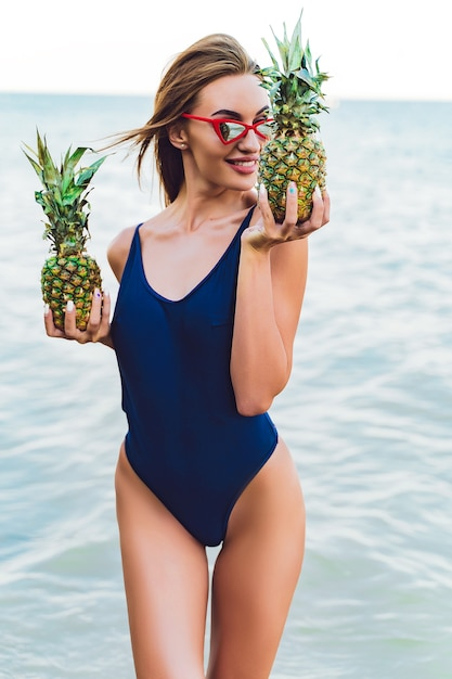 Modelo de menina em um monokini na costa do mar de uma ilha tropical segurando dois abacaxis Foto Premium