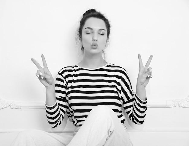 Modelo de menina morena linda com maquiagem nude em roupas de verão hipster posando perto da parede. sentado no chão, dando beijo e mostrando sinal de paz Foto gratuita
