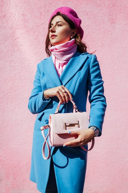 Modelo de moda de beleza. mulher segurando uma bolsa elegante e vestindo casaco azul. roupas femininas de outono e acessórios. Foto Premium