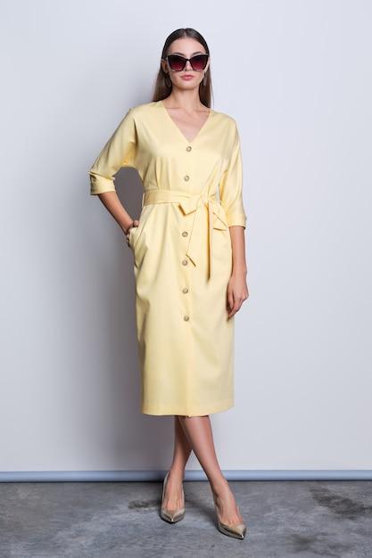 Modelo de moda em grandes óculos de sol com vestido amarelo com botões posando sobre fundo cinza Foto Premium