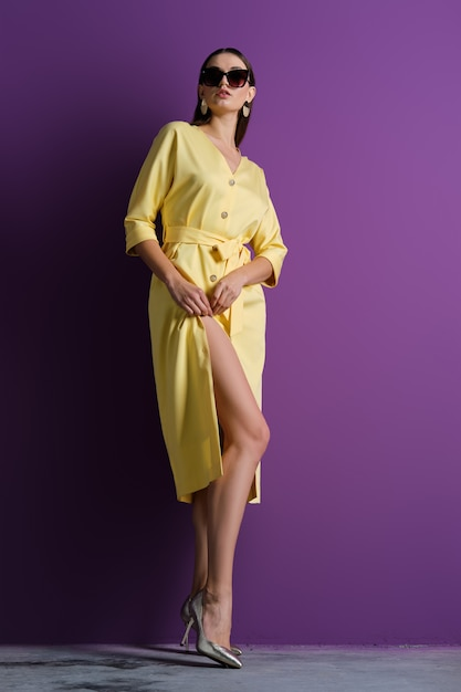 Modelo de moda em grandes óculos de sol, vestido amarelo com botões abertos Foto Premium