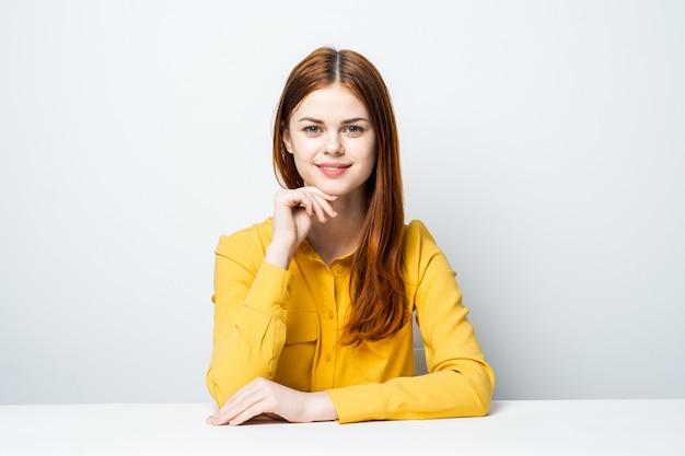 Modelo de mulher bonita na mesa em uma camisa amarela coloca emoções diferentes Foto Premium