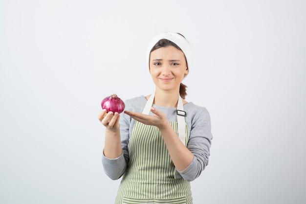 Modelo de mulher bonita no avental segurando uma cebola roxa. Foto gratuita