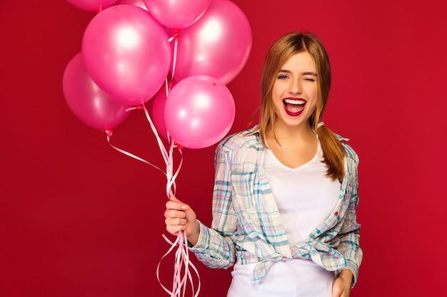 Modelo de mulher com balões de ar rosa. piscando Foto gratuita